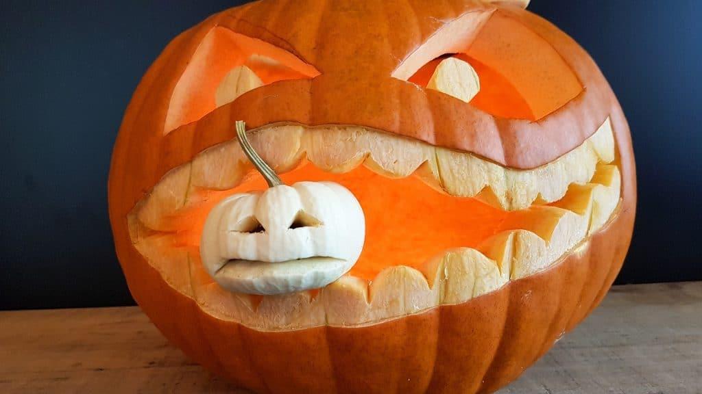 "Carved pumpkin ""eating"" a small, baby pumpkin"