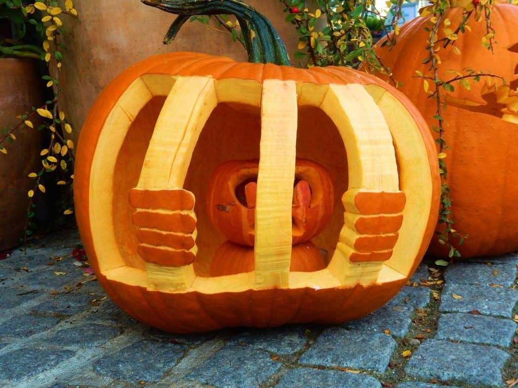 Pumpkin carving with a pumpkin behind bars